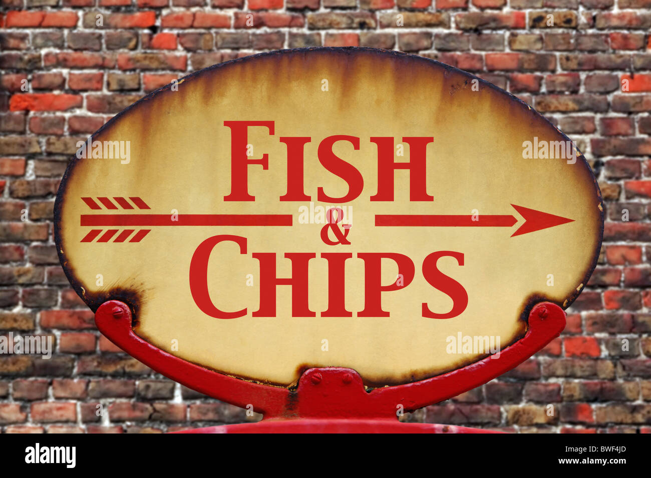 A rusty old retro arrow sign with the text Fish and chips - Stock Image