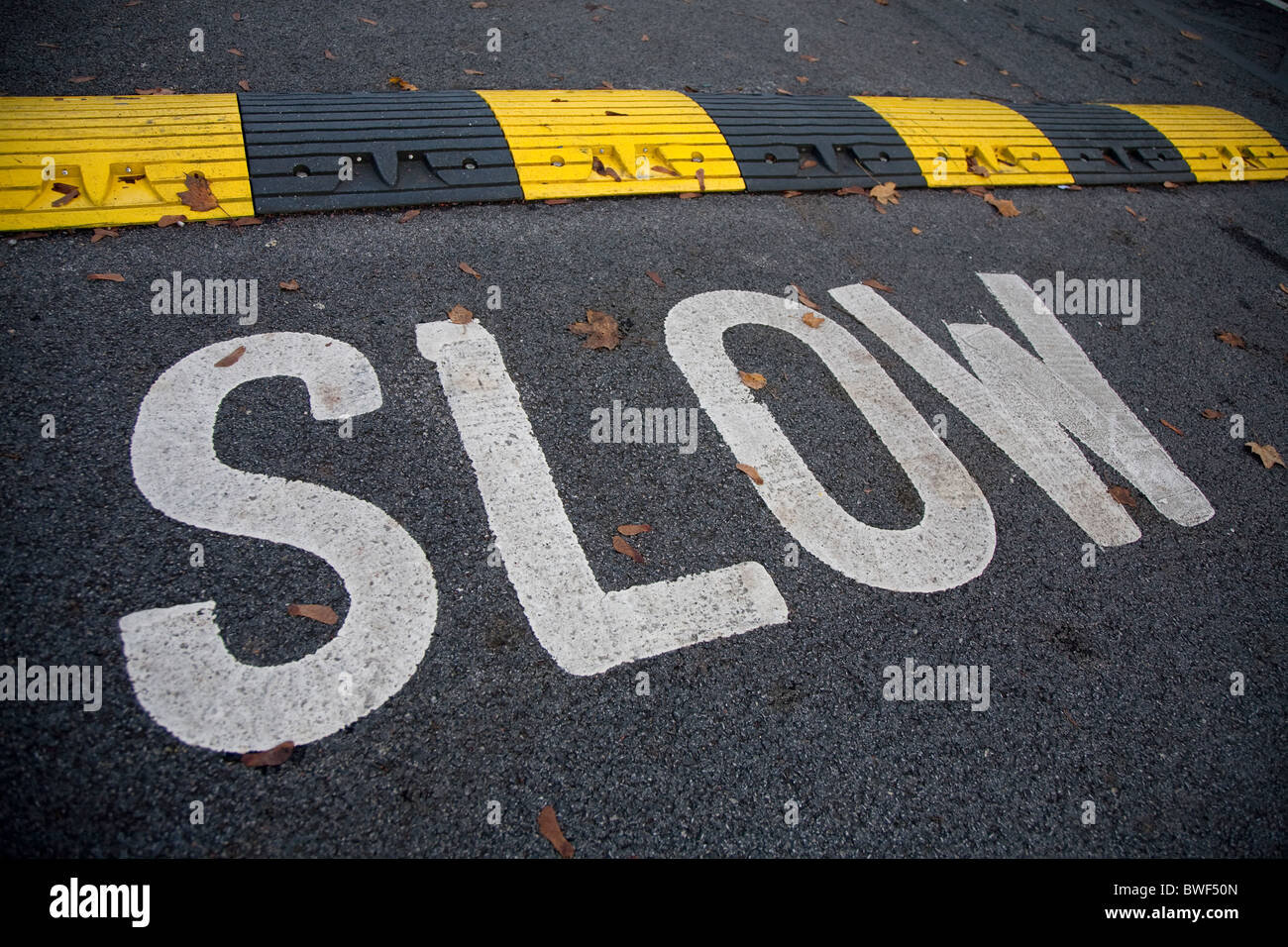 yellow and black sleeping policeman speed hump and slow sign on tarmac road - Stock Image
