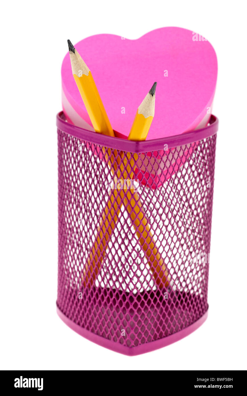Pink pencil pot and yellow pencils with heart shaped jotter pad - Stock Image