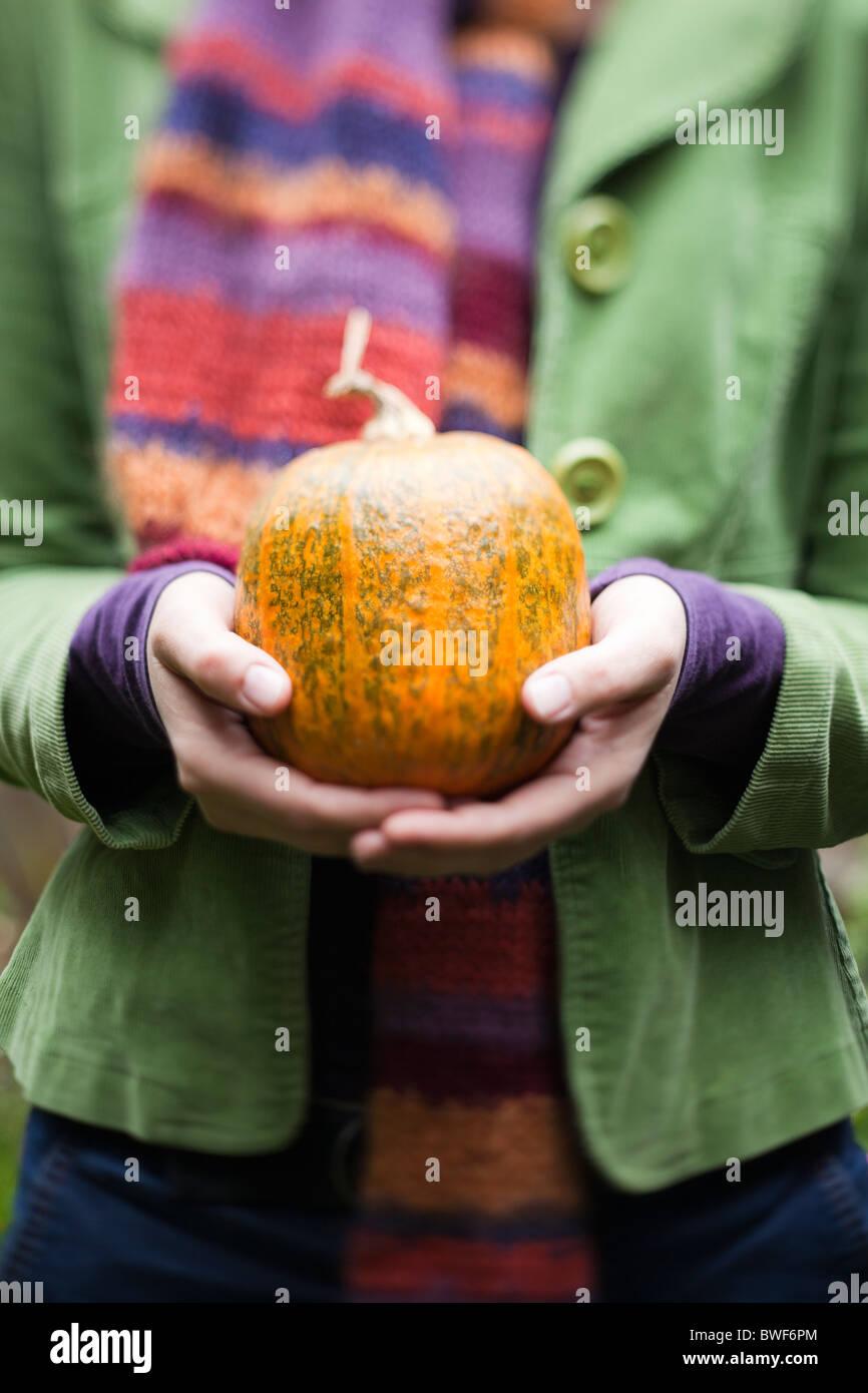 Woman holding a home grown pumpkin - Stock Image
