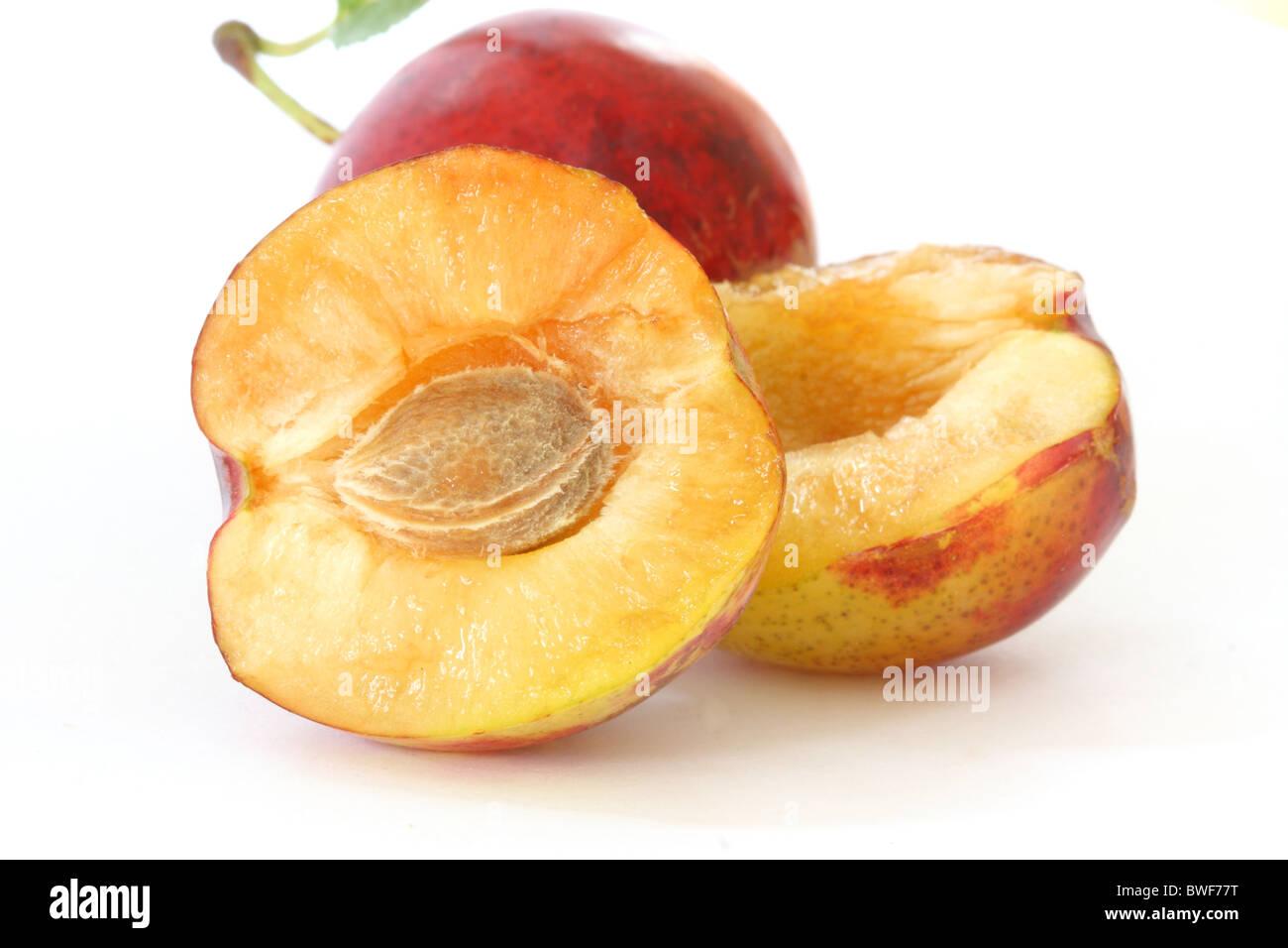 Three fresh plums on white background - one opened Stock Photo