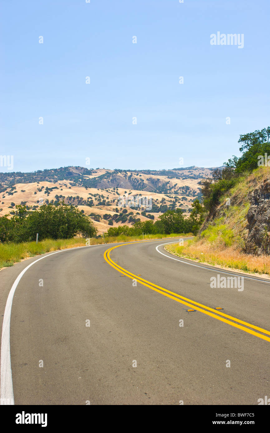 Empty paved road with yellow double line - Stock Image