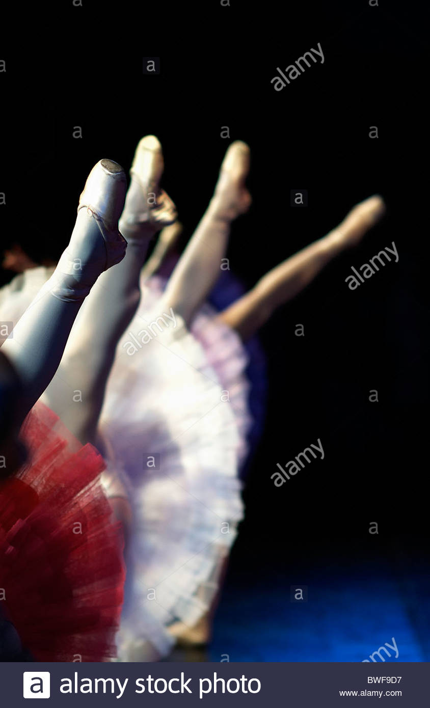 Four ballet dancers with there legs in the air.  Closest shoe in focus. En Pointe different coloured tutus. - Stock Image
