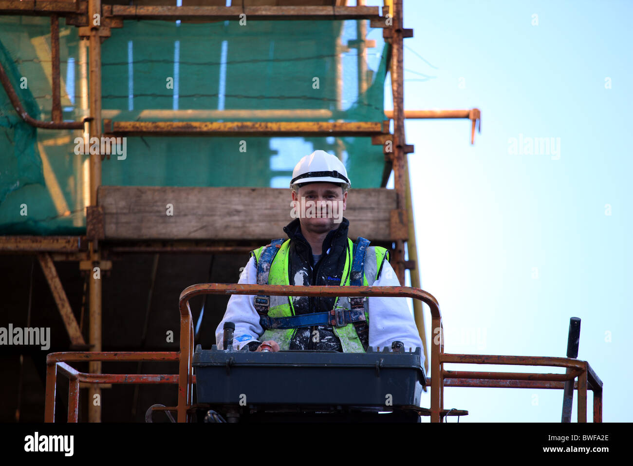 Workman on hoist wearing safety harness and hard hat - Stock Image