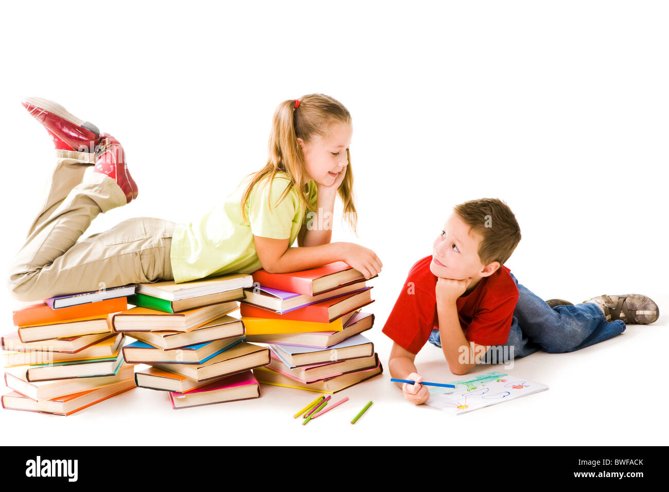 Smart girl lying on top of book piles and talking to cute schoolboy drawing near by - Stock Image