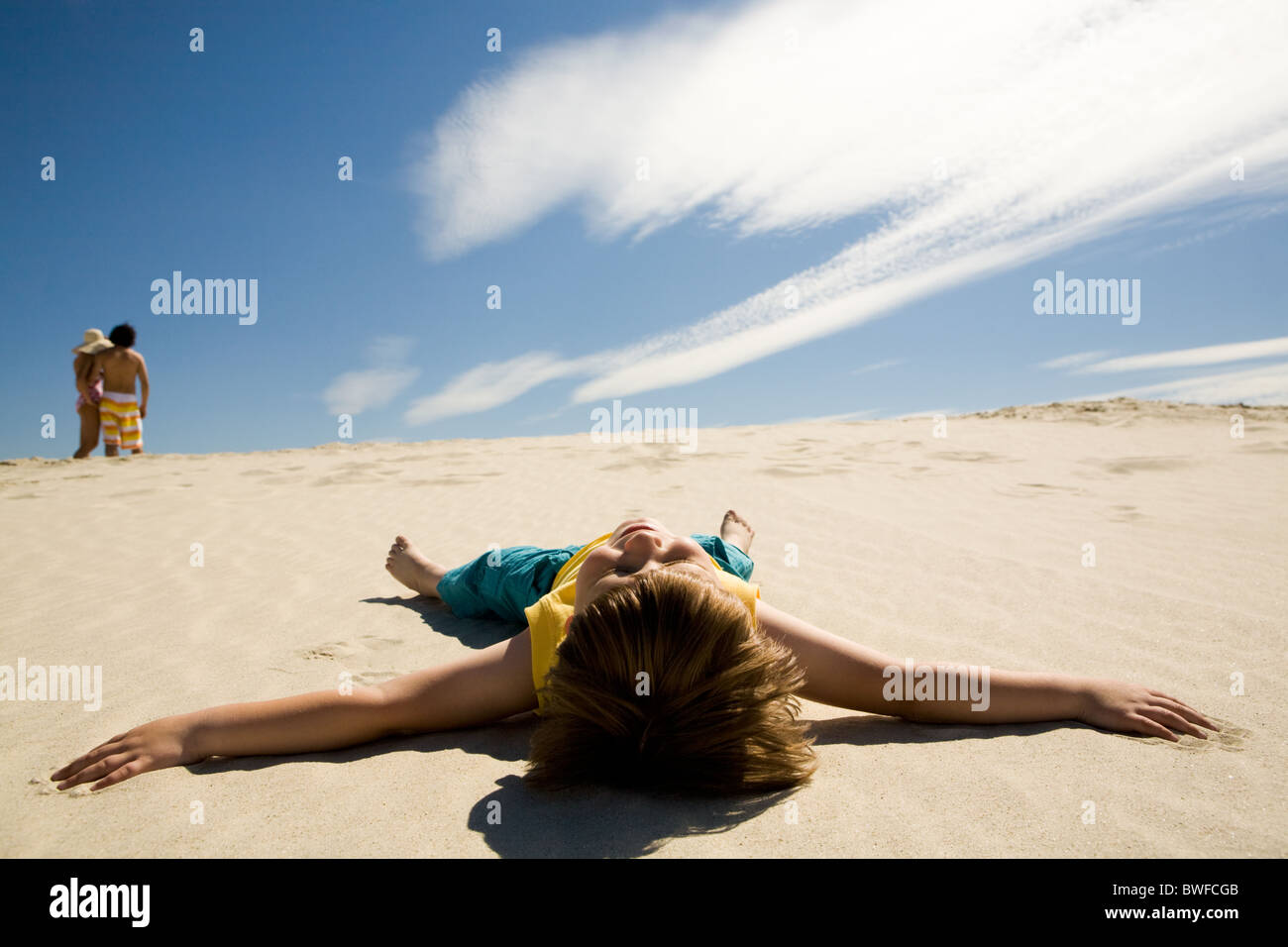 Image of restful boy lying on sand under blue sky and enjoying sunny day - Stock Image
