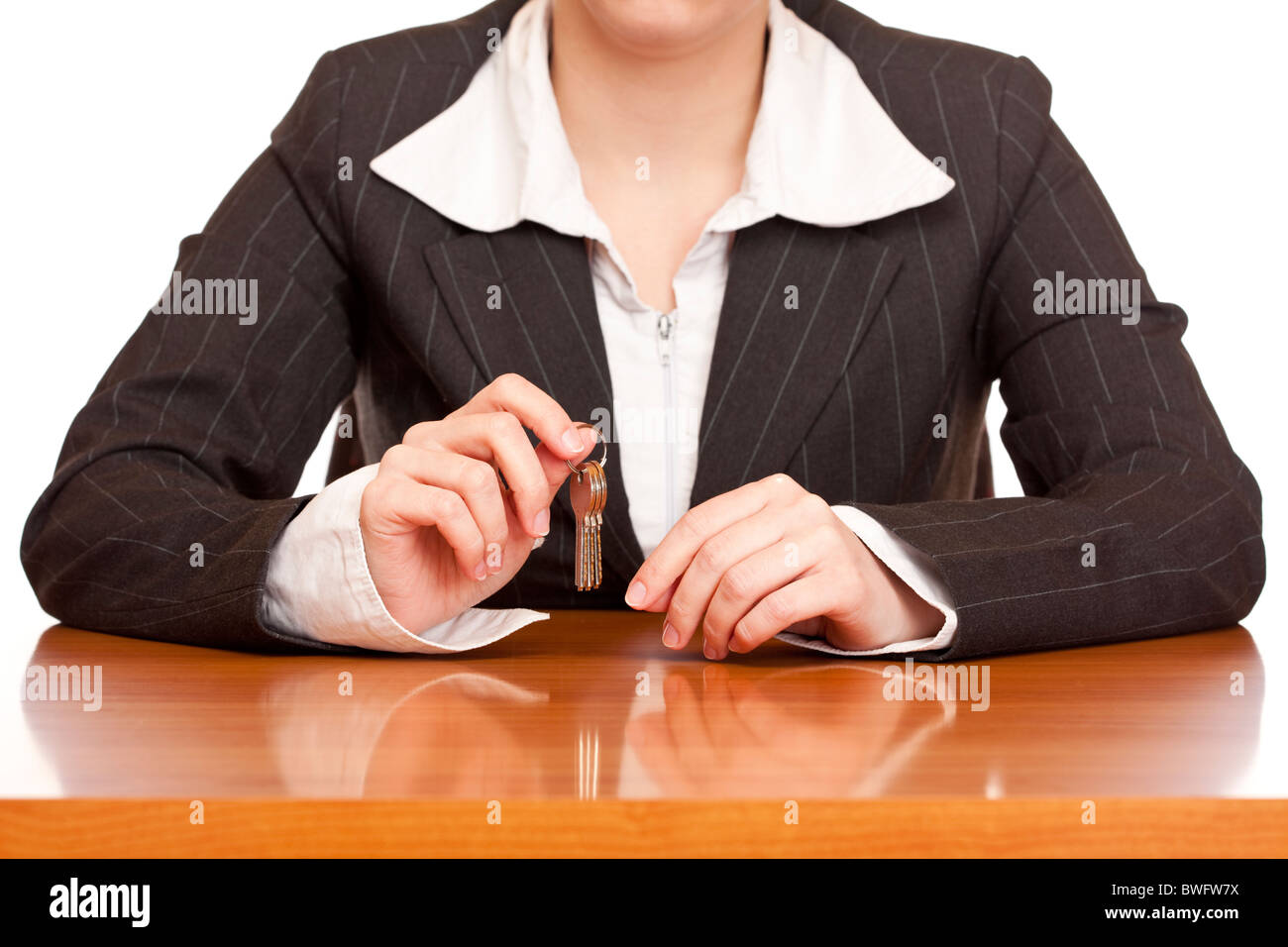 Business woman holds house key for handing over of keys. Isolated on white background. - Stock Image