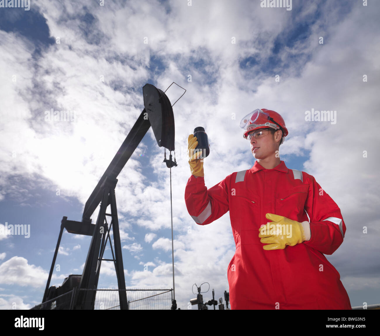 Worker inspecting crude oil at oil well - Stock Image