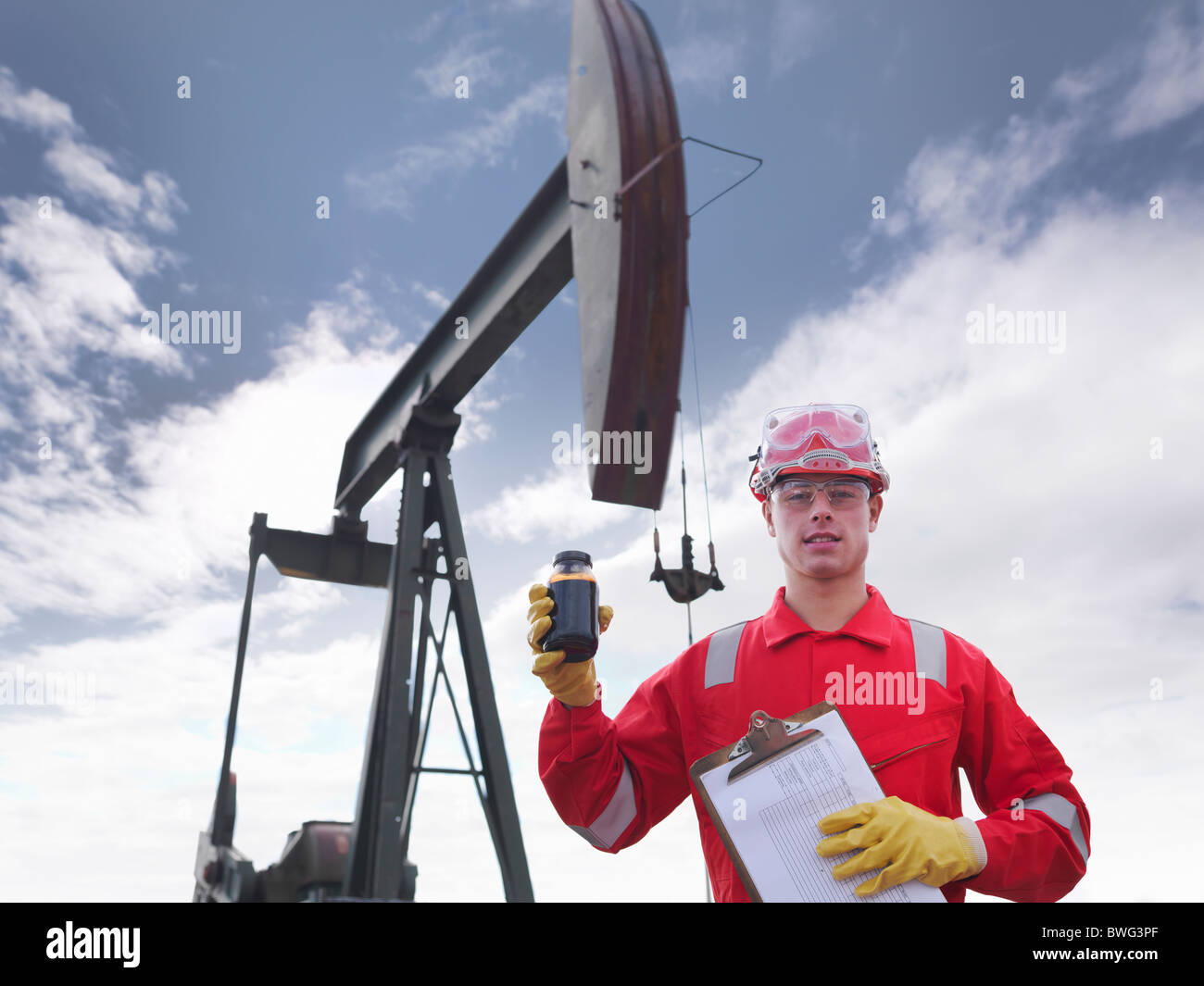 Worker holding crude oil at oil well - Stock Image