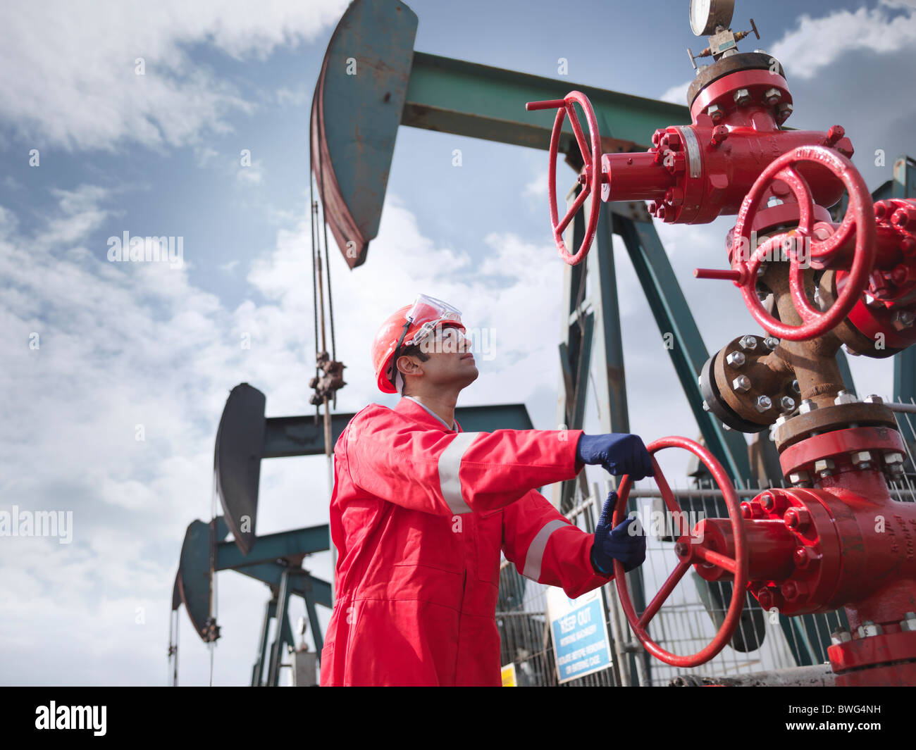 Worker turning valve on oil well - Stock Image