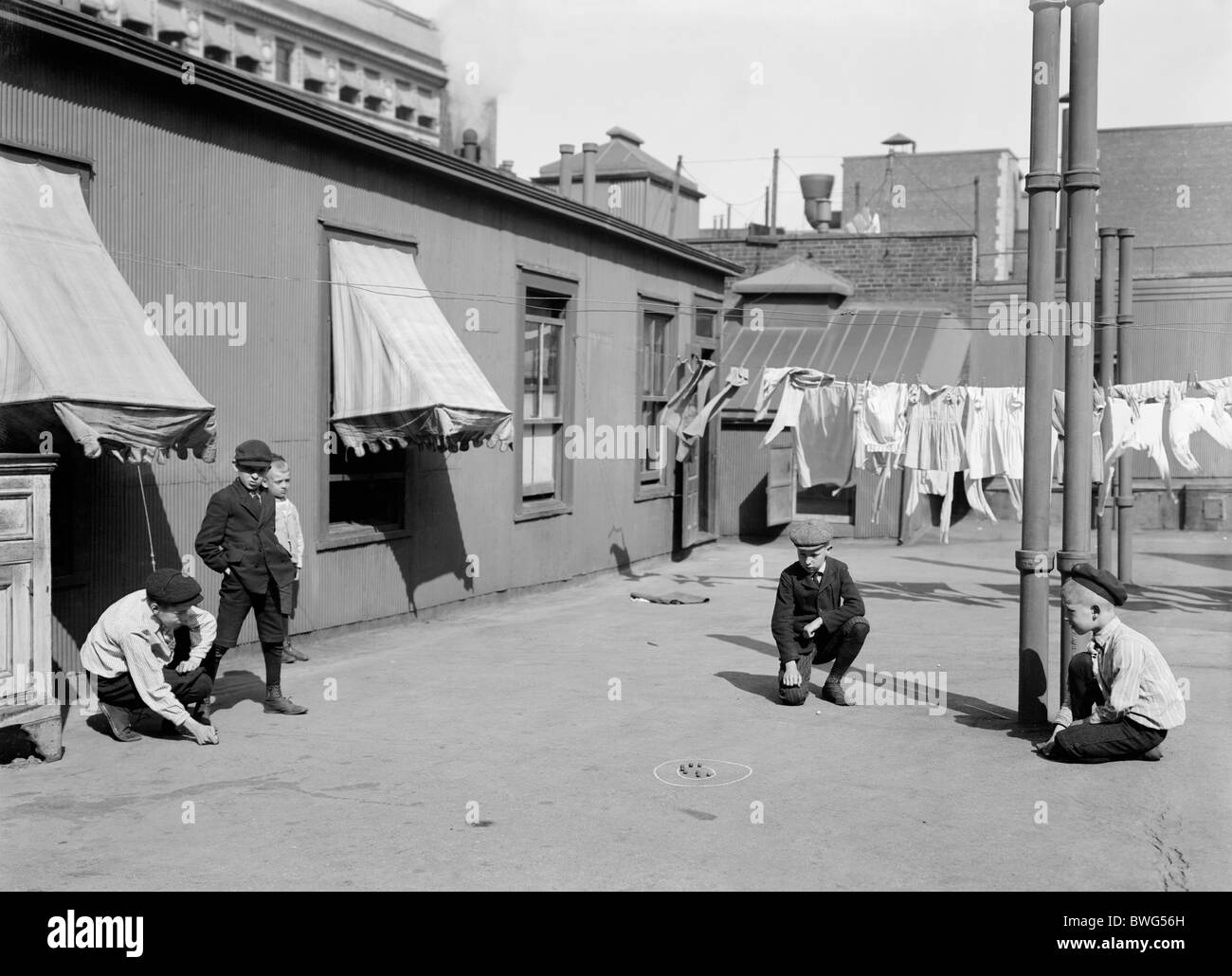 """Vintage photo c1910 of young boys playing marbles on the roof of a """"skyscraper"""" apartment building in New York City. Stock Photo"""