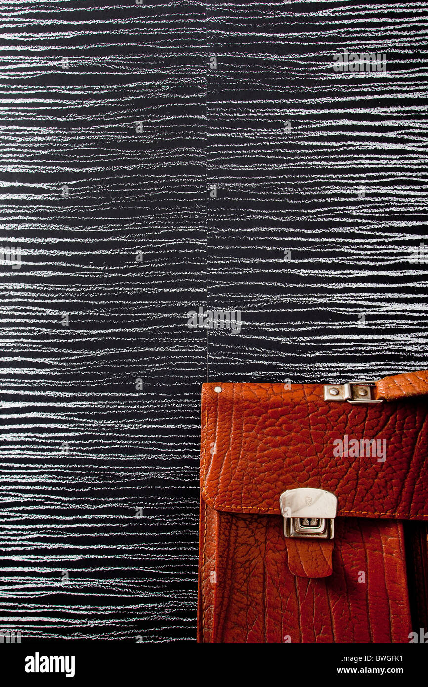 Part of a brown briefcase on streaky wallpaper.Sweden - Stock Image