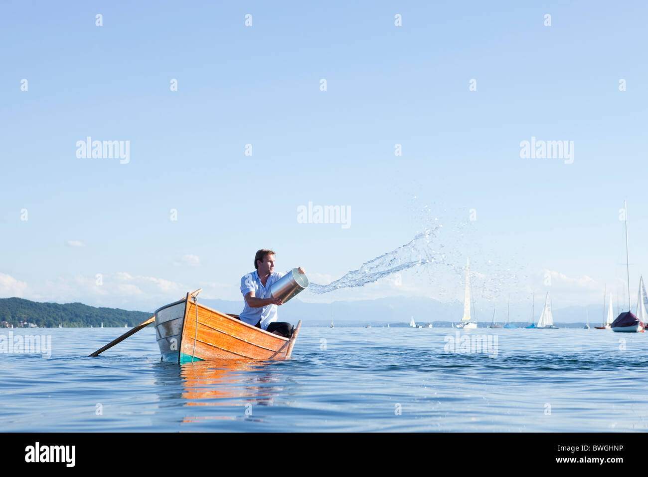 Throwing buckets of water ot ouf boat - Stock Image