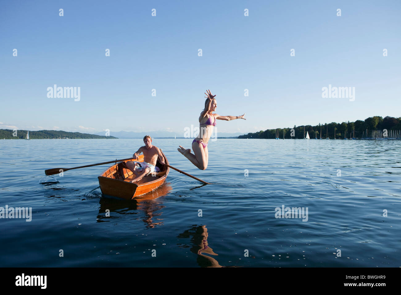 Young woman jumping off a row boat - Stock Image
