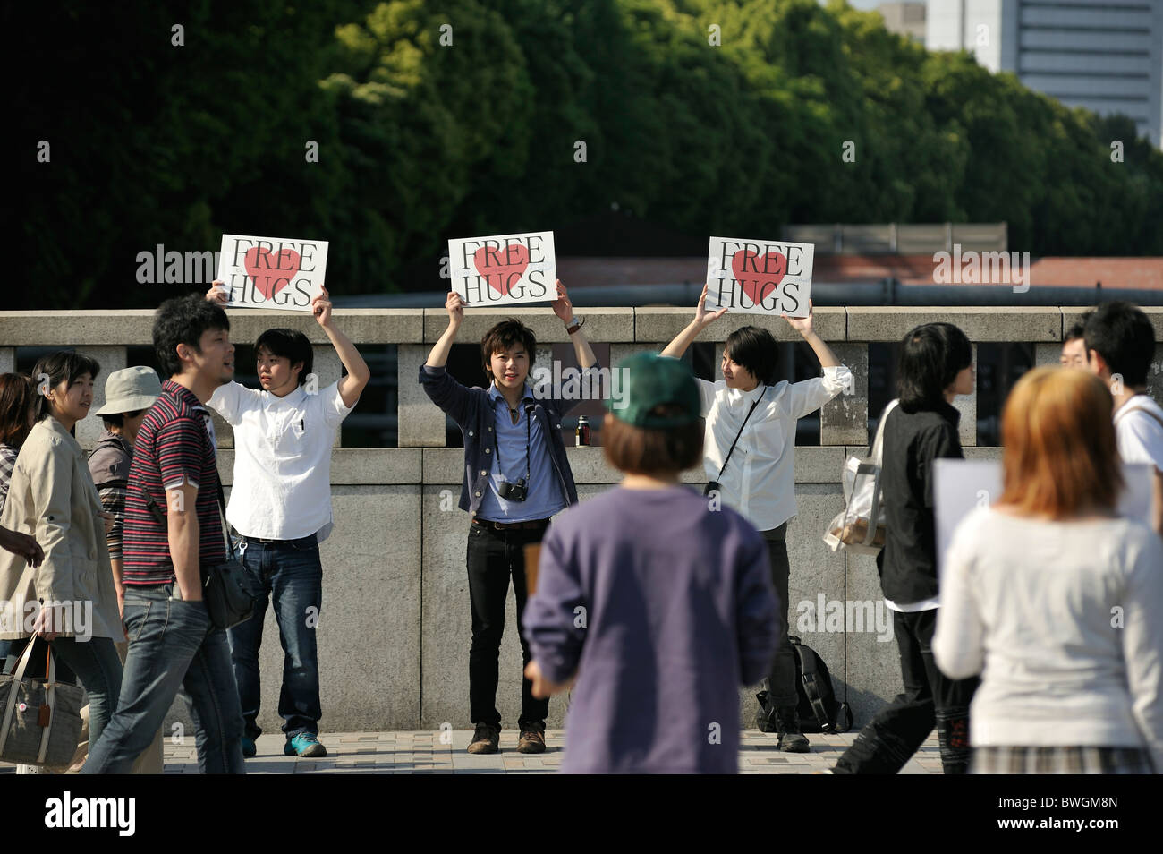 Young Japanese men offering 'free hugs' on the Jingu bridge, Harajuku, Tokyo, Japan - Stock Image