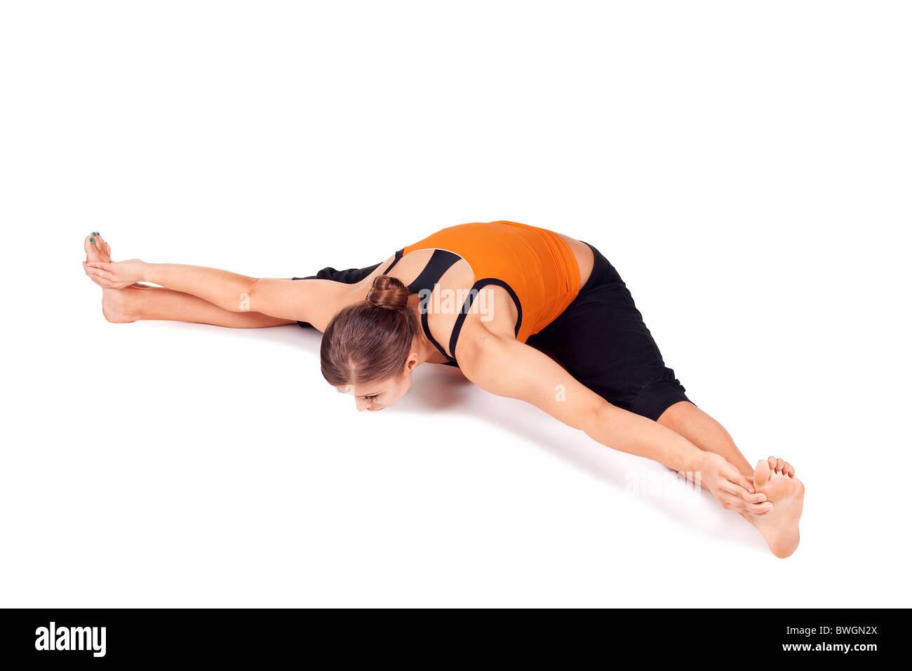 Woman doing yoga exercise called Seated Wide Angle Pose, Sanskrit name: Upavista Konasana - Stock Image