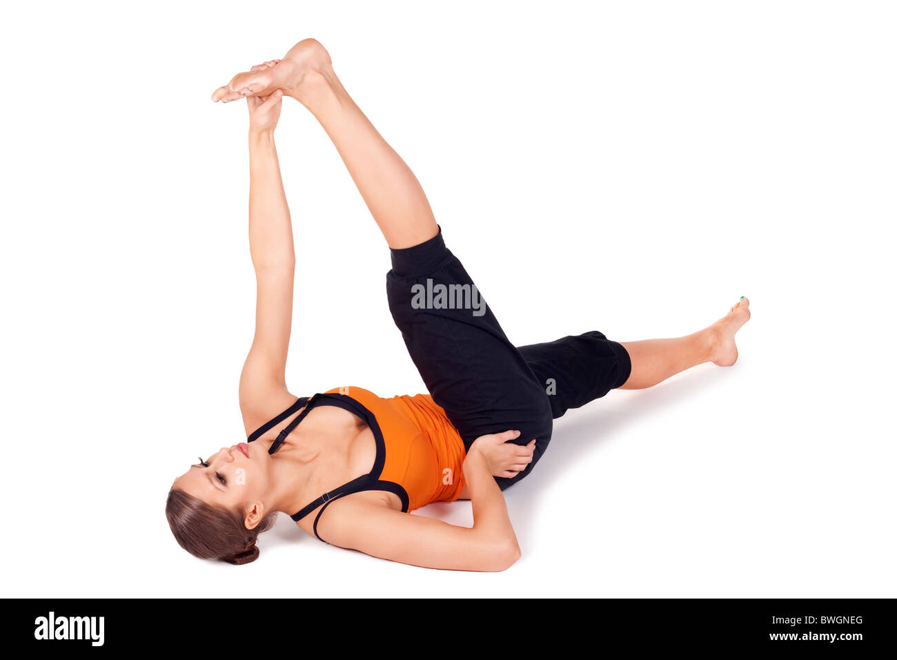 Woman doing Reclining Big Toe yoga pose (there are four versions of this exercise), Sanskrit name: Supta Padangusthasana - Stock Image
