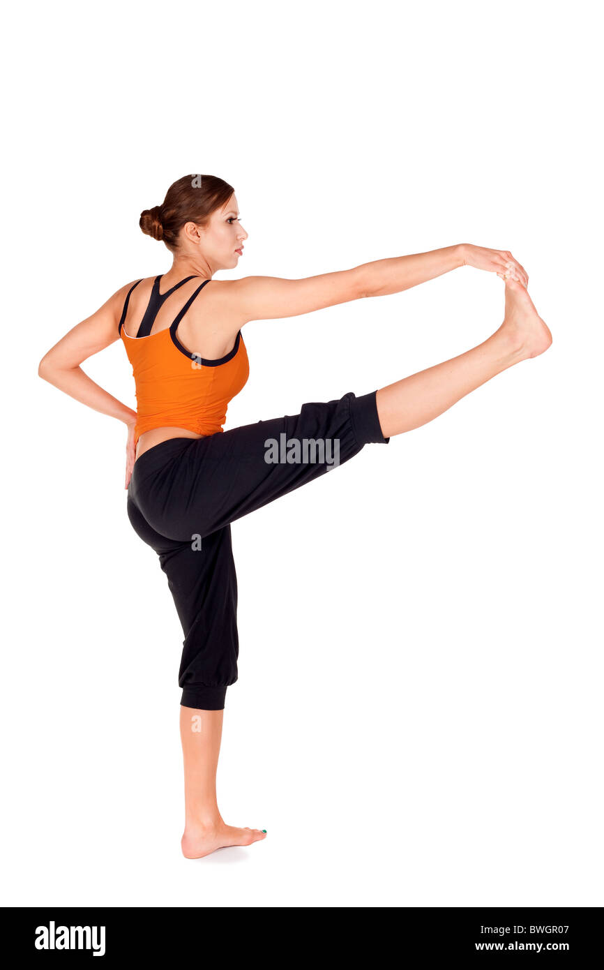 Woman doing first stage of yoga exercise called: Revolved Hand to Big Toe Pose, Sanskrit name: Hasta Padangusthasana - Stock Image