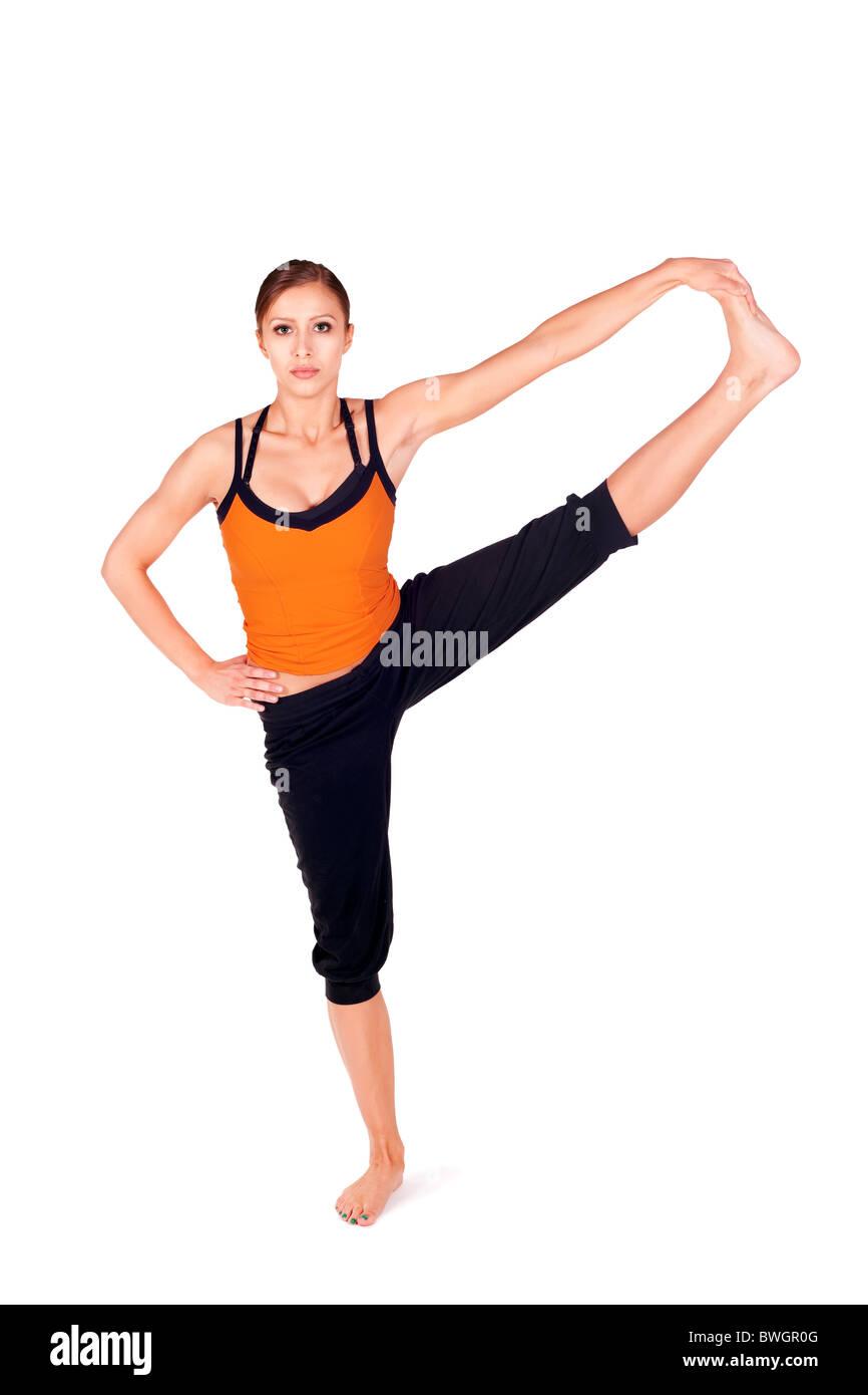 Woman doing yoga exercise called: Revolved Hand to Big Toe Pose, Sanskrit name: Hasta Padangusthasana - Stock Image