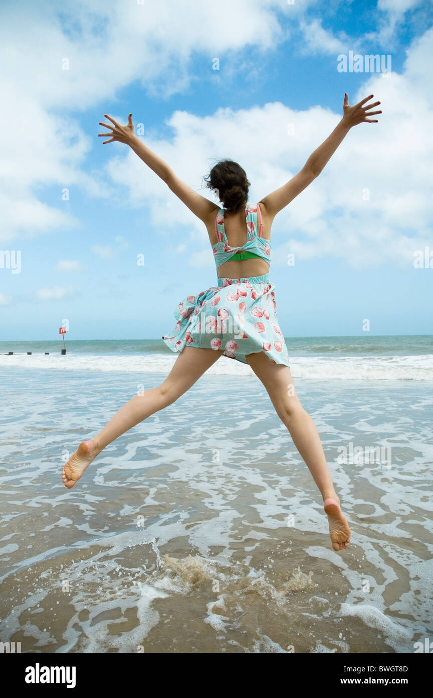 Girl leaps on waters edge - Stock Image