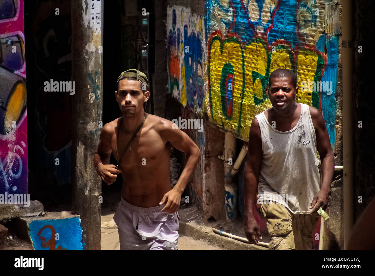 Brazilian men walk in front of the wall covered by graffiti in Rocinha, the largest slum in Rio de Janeiro. - Stock Image