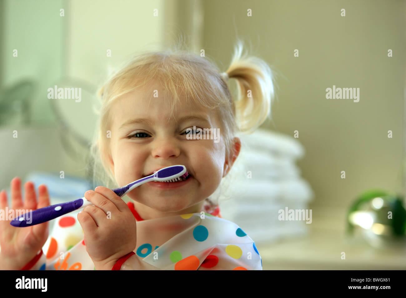 2 year old girl brushing her teeth - Stock Image