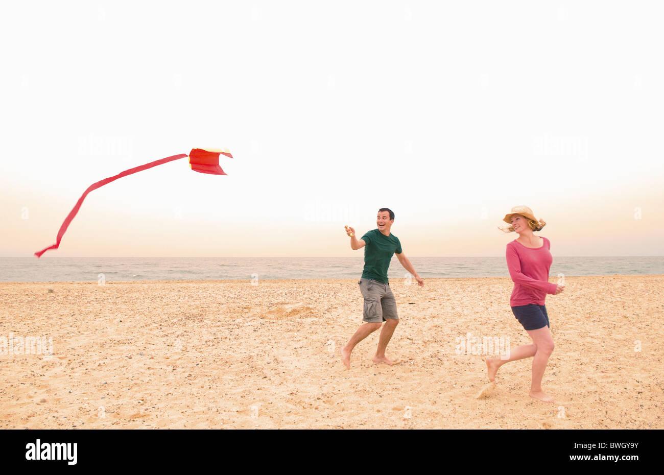Happy couple fly kite on beach - Stock Image