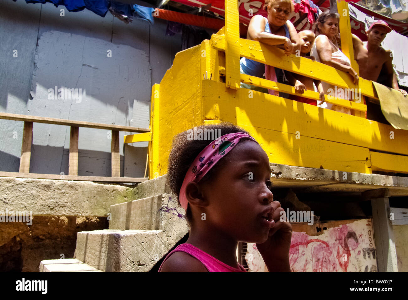 A Brazilian girl talks in front of her family in Rocinha, the largest slum in Rio de Janeiro. - Stock Image