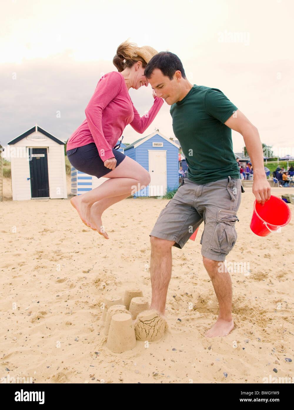 Couple destroy sandcastles - Stock Image