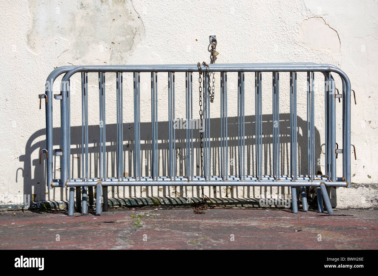 England, West Sussex, Bognor Regis, Galvanized crowd control barriers chained to a wall. - Stock Image