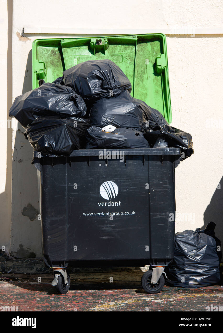 England, West Sussex, Bognor Regis, Wheeled waste bin container overflowing with full large black refuse sacks and - Stock Image