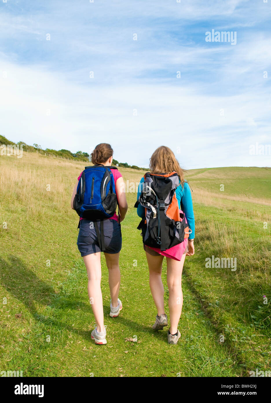 Two young women hikers climb up hill - Stock Image
