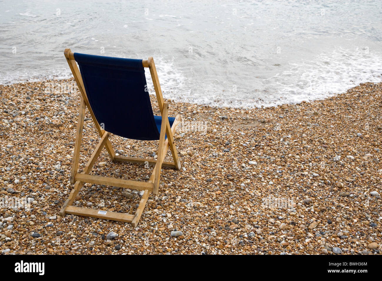 England West Sussex Bognor Regis Single dark blue deck chair on pebble shingle beach looking out to sea with gentle - Stock Image