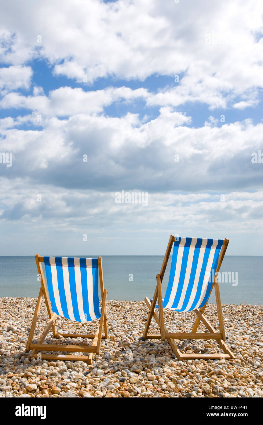 England, West Sussex, Bognor Regis, Two blue and white deck chair on the shingle pebble beach looking out to sea. - Stock Image