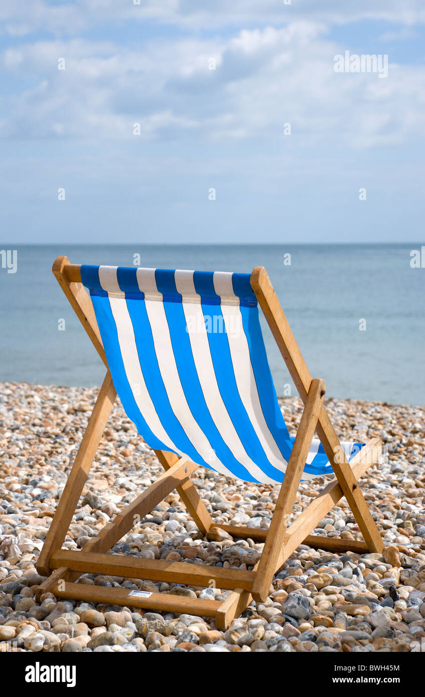 England, West Sussex, Bognor Regis, Single blue and white deck chair on the shingle pebble beach looking out to - Stock Image