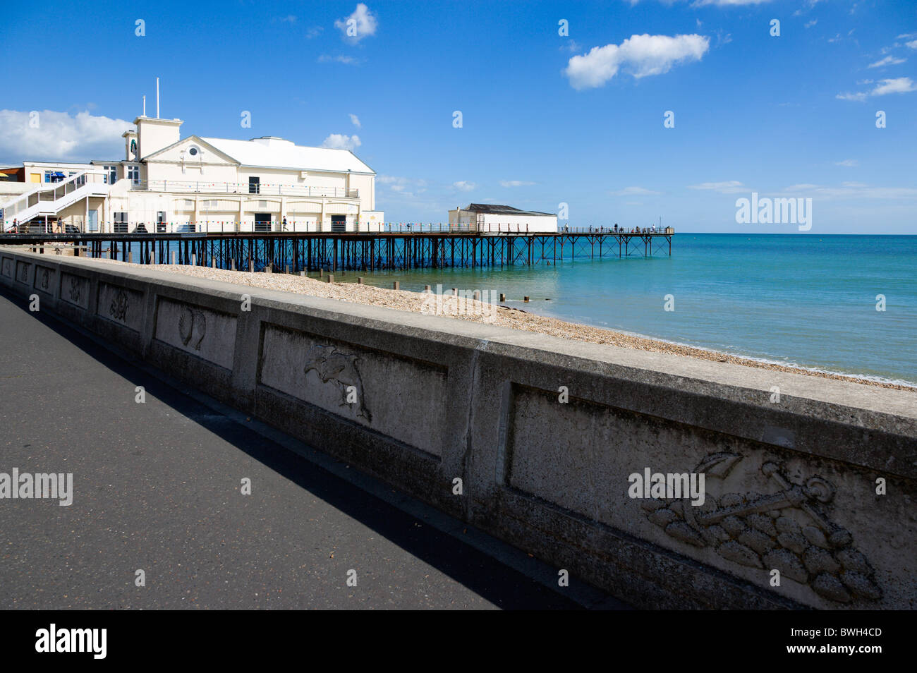 England West Sussex Bognor Regis Pier and people fishing off the end and with pebble beach and promenade sea defense - Stock Image