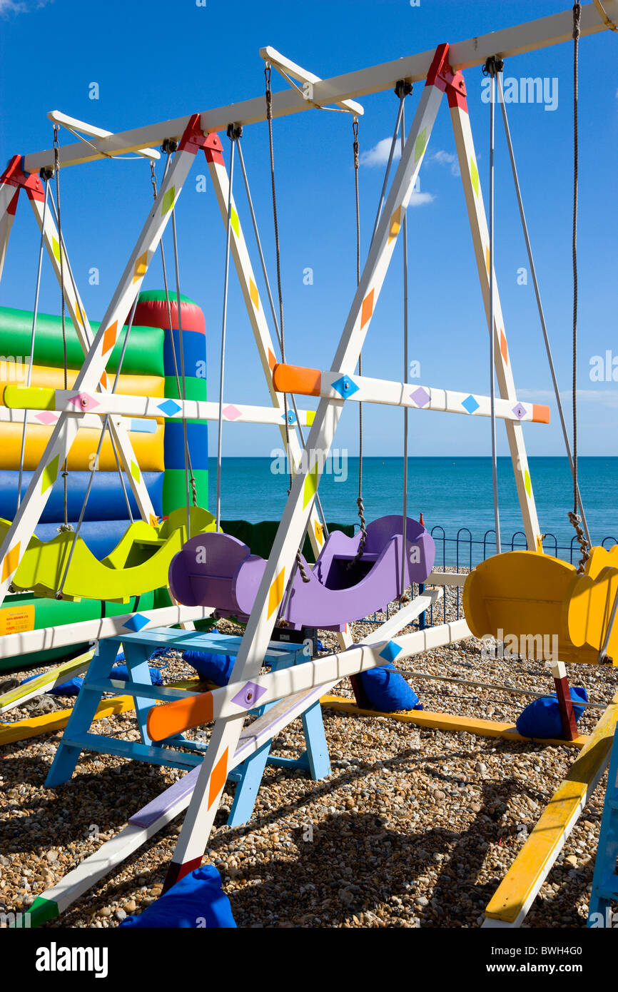 England West Sussex Bognor Regis Colourful amusement swings on the pebble shingle beach by the promenade. - Stock Image