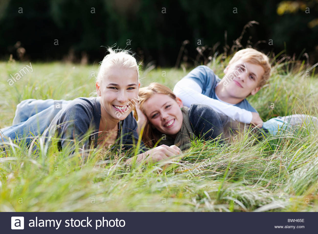 Three young persons laying in grass - Stock Image