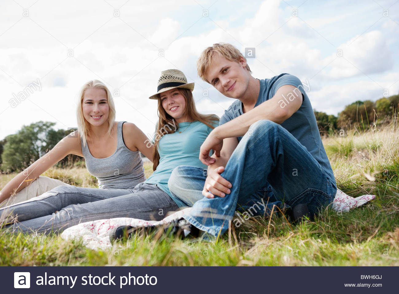 Three young persons sitting in grass - Stock Image