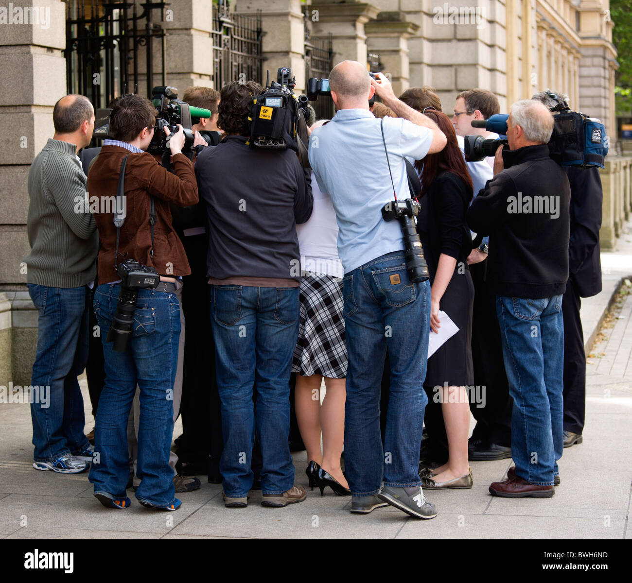 Ireland County  Dublin City News Media Press photographers cameramen and journalists surround politician on pavement - Stock Image