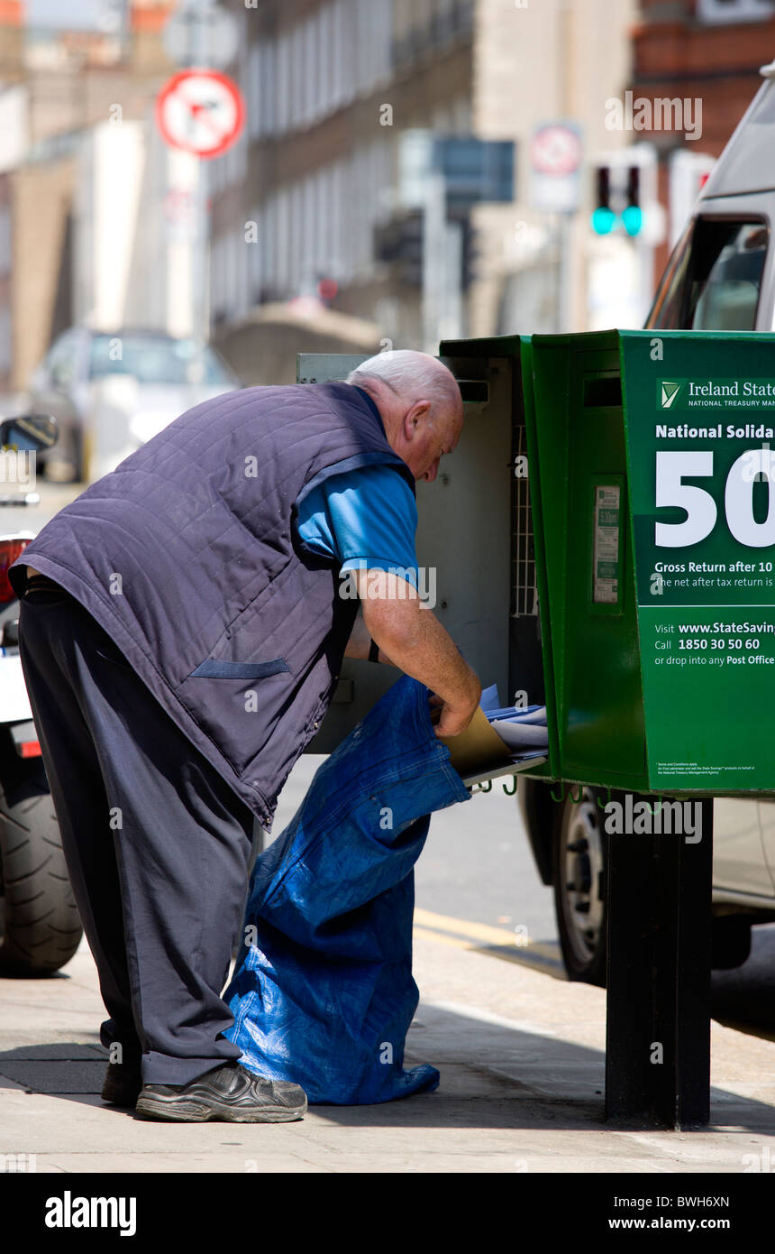 Ireland County Dublin City Post Irish postal worker emptying mail from green modern letterbox into sack on pavement - Stock Image