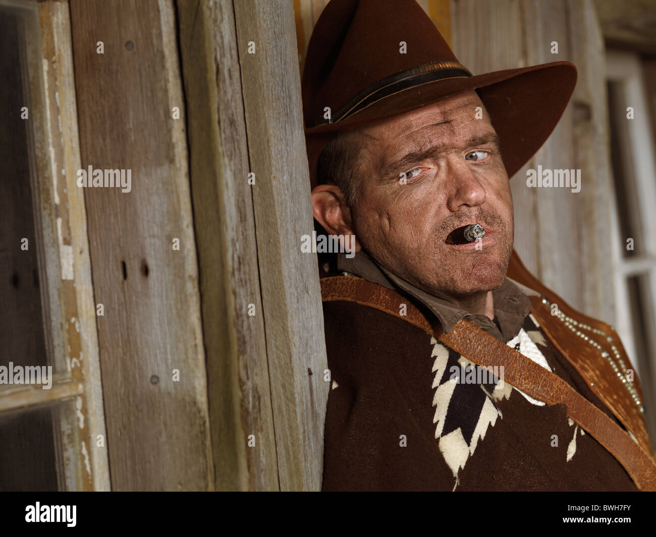 Dramatic portrait of a cowboy leaning against a wall of a wooden house with a cigar in his mouth - Stock Image