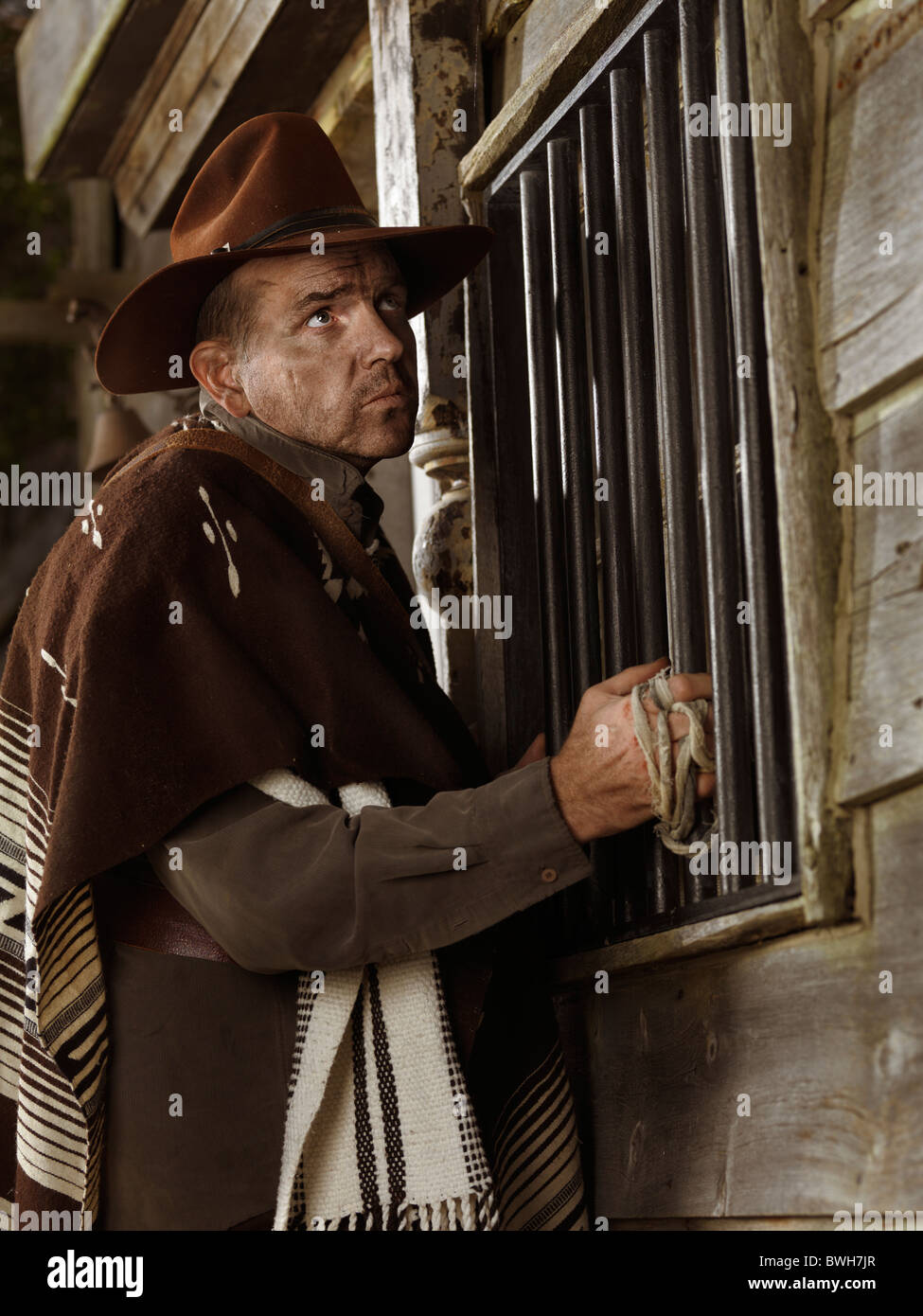 Cowboy standing at a barred window, attempting to rob a bank at night - Stock Image