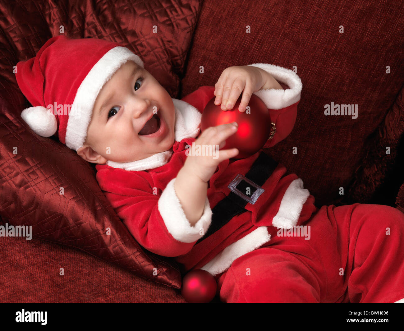 8aaa125e6 Happy smiling six month old baby boy in Santa Christmas costume lying on a  sofa with a red bauble in his hands