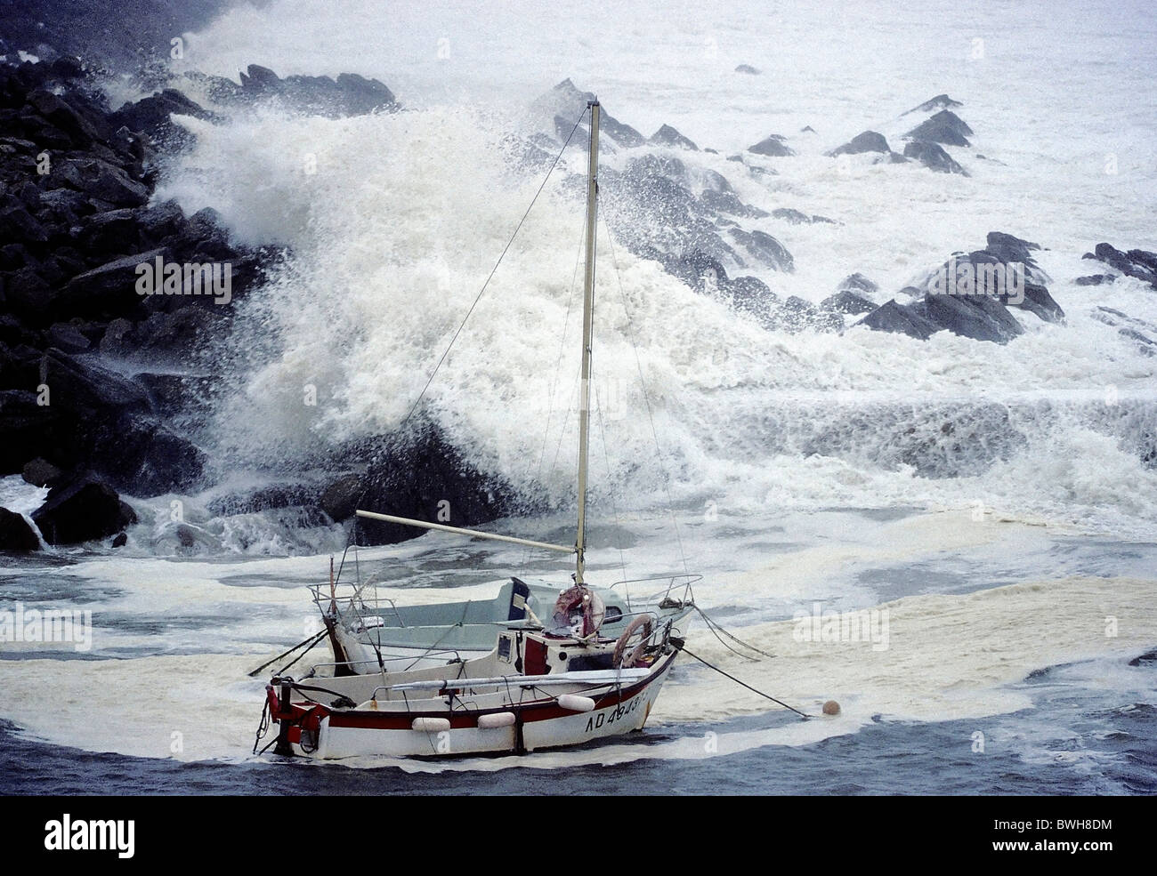 High waves crashing over rocks, rocking small boats, stormy seas on the Brittany coast, hurricane, Finistere, Brittany, - Stock Image