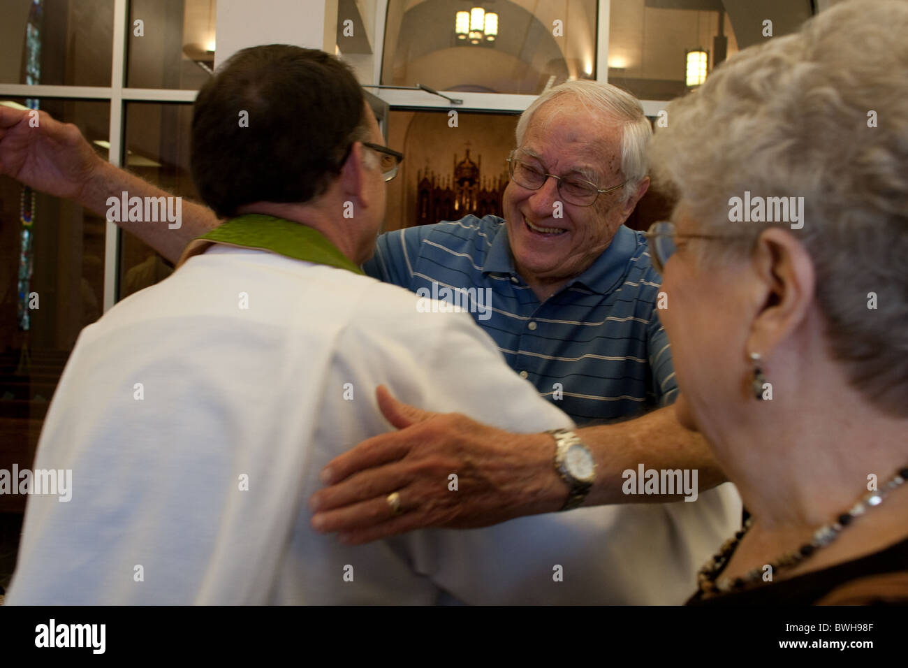Anglo male congregation member greets pastor with a hug as he leaves Sunday morning service at St. Martin's - Stock Image