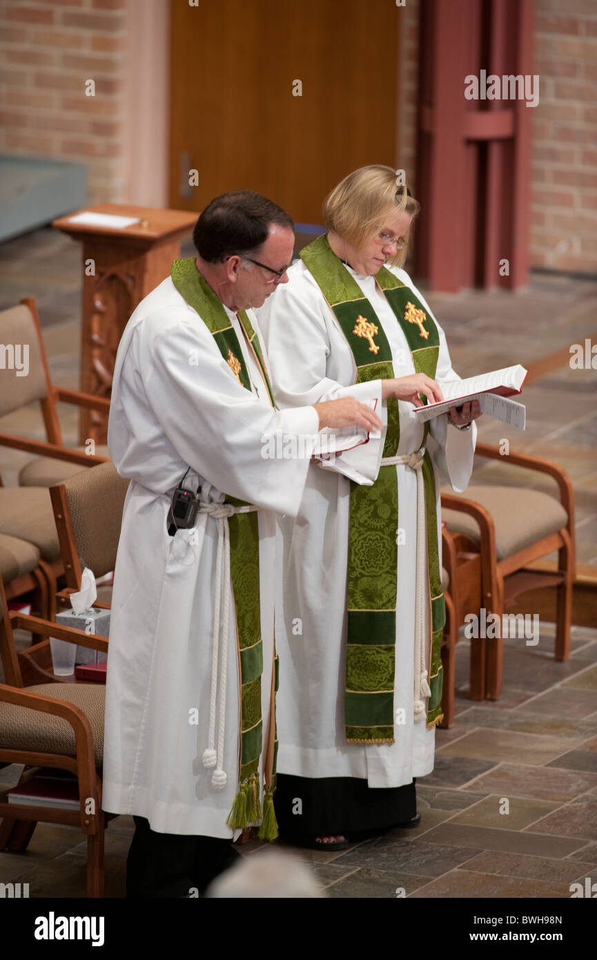Anglo male presiding minister and Anglo female assisting minister look at their prayer books during Sunday church - Stock Image