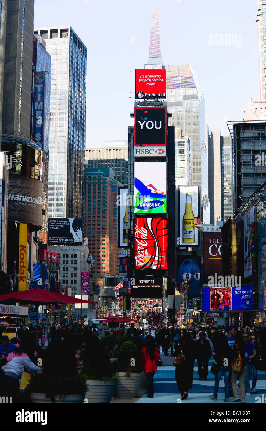 USA, New York, Manhattan, People walking in Times Square at the junction of 7th Avenue and Broadway below advertising - Stock Image