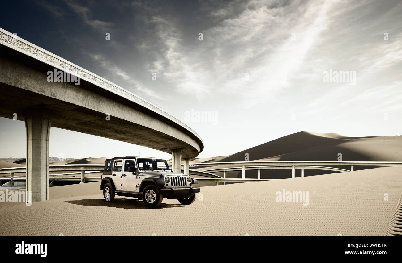 Transportation Jeep front 3/4 static beauty in dunes with freeway overpass - Stock Image