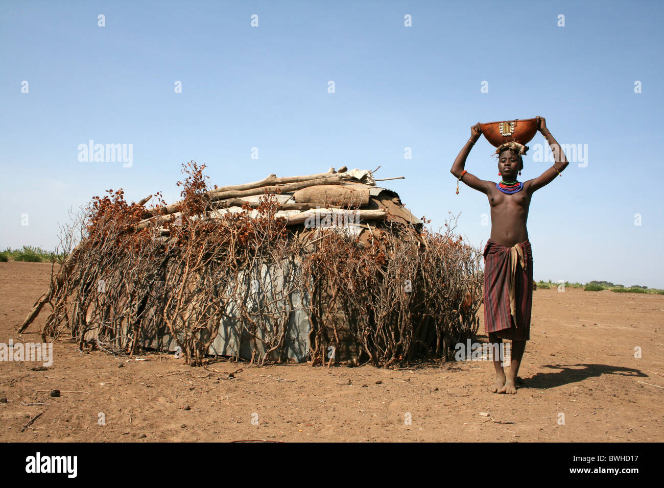 Dassanech Tribeswoman Standing Outside Her Hut, Omorate, Omo Valley, Ethiopia - Stock Image